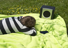 Enjoying music from wireless and portable speakers. Young boy laying on a blanket in the grass listening to music streaming frpm his smartphone to a wireless and Stock Photos