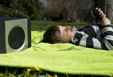 Enjoying music from wireless and portable speakers. Young boy laying on a blanket in the grass listening to music streaming frpm his smartphone to a wireless and Stock Images