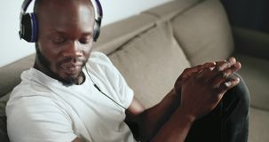 Enjoying the Music. Young afro-american man dressed in white t-shirt wears headphones enjoying music sitting on grey sofa, indoors close up shot stock video footage