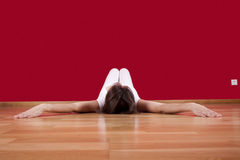 Enjoying my new home. Woman laying on the floor of her house next to a red wall Stock Photos