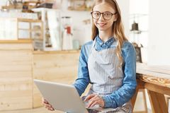 Smart young lady sitting straight with laptop royalty free stock image