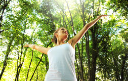 Enjoying the nature. Young beautiful woman arms raised enjoying the nature in green forest Royalty Free Stock Photo