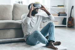 Enjoying new reality!. Handsome young African man adjusting his VR headset while sitting on the carpet at home Stock Photography