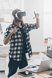Enjoying new reality. Handsome young man with long hair in virtual reality headset gesturing while standing in creative office Stock Photos