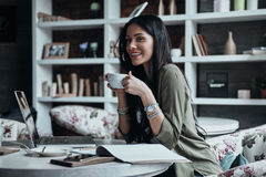 Enjoying nice day. Beautiful young woman holding a cup and looking away with smile while sitting at her working place in the cafe Royalty Free Stock Photography