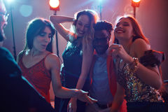 Enjoying night in club. Stylish Afro-American in sunglasses dancing joyfully in night club and embracing two pretty women with wide smiles on their faces Stock Image