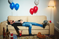Enjoying night after wild party. Smiling middle-aged man lying on couch and drinking beer from bottle in messy living room, empty alcohol bottles and plastic Royalty Free Stock Images