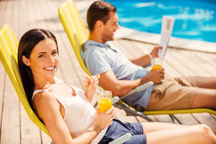 Enjoying orange fresh poolside. Stock Photography