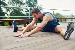 Enjoying Outdoor Workout. Young sporty man with closed eyes doing stretching exercise and enjoying fresh air while sitting on wooden floor of spacious terrace Stock Photo