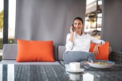 Pleased young lady looking away while talking on the phone royalty free stock photography