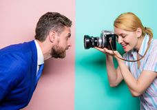 Enjoying photo shoot session. Photographer shooting male model in studio. Pretty woman using professional camera. Businessman posing in front of female royalty free stock photo