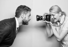 Enjoying photo shoot session. Photographer shooting male model in studio. Pretty woman using professional camera stock images