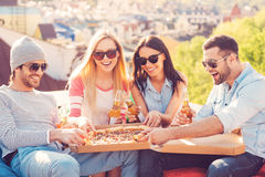 Enjoying pizza with friends. Royalty Free Stock Photo