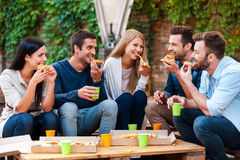 Enjoying pizza together. Stock Image