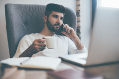 Enjoying quick coffee break. Confident young man working on laptop and drinking from coffee cup while sitting in office or cafe Stock Photo