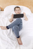 Enjoying Reading. Elementry school boy reading his tablet before he goes to bed Royalty Free Stock Images