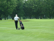 Enjoying Retirement. An elderly man enjoying his retirement on the golf course Stock Photos