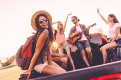 Enjoying road trip with best friends. Group of young cheerful people dancing and playing guitar while enjoying their road trip in pick-up truck together Stock Photos