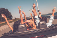 Enjoying road trip. Rear view of young happy people enjoying road trip in their convertible and raising their arms up Stock Photography