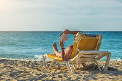 Enjoying the sea and sun. Funny looking man tanning on the beach. Stock Images