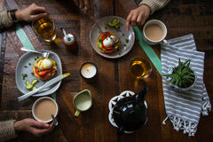 Enjoying a simple meal on a wooden table. Hands, tea and a simple meal atop a wooden table Stock Photo