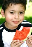 Enjoying a slice of watermelon. Beautiful little boy enjoying a slice of juicy red watermelon, in the summer's outdoor stock photography