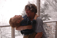 Enjoying The Snow. A grandmother tips her grandson back so he can catch snowflakes in his mouth. On a whim, they rushed outside onto the deck – and into the Royalty Free Stock Image