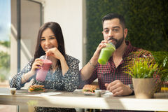 Enjoying some healthy drinks. Attractive young couple having some smoothies and sandwiches during a lunch date Royalty Free Stock Image
