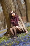 Enjoying spring. Beautiful woman sitting under the tree enjoys first days of spring Royalty Free Stock Photos