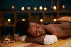 Enjoying stone massage Royalty Free Stock Image