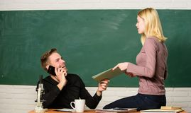 Enjoying students life. University or college students. Pretty teacher and handsome schoolmaster grading papers. Couple. Studying in classroom. Man and woman stock photo