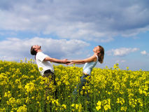 Enjoying summer. Young couple having fun in summer rape field Royalty Free Stock Images