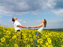 Enjoying summer. Young couple having fun in summer rape field Royalty Free Stock Photography