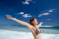 Enjoying the summer. Beautiful young woman with arms open in a tropical beach enjoying the summer Stock Photos