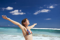 Enjoying the summer. Beautiful young woman with arms open in a tropical beach enjoying the summer Stock Images