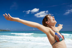 Enjoying the summer. Beautiful young woman with arms open in a tropical beach enjoying the summer Stock Image