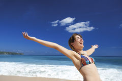 Enjoying the summer. Beautiful young woman with arms open in a tropical beach enjoying the summer Stock Photography