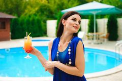 Enjoying summer. Beautiful young woman drinking cocktail while relaxing near the pool. royalty free stock images