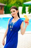 Enjoying summer. Beautiful young woman drinking cocktail while relaxing near the pool. royalty free stock photos