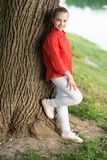 Enjoying summer holidays. Small girl relaxing at tree on summer day. Adorable child with long blond hair in casual style stock image