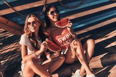 Enjoying summer refreshments. Top view of two attractive young women smiling and eating watermelon sitting outdoors stock image