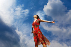 Enjoying the sun. Pretty young woman with arms raised standing almost weightlessly towards the sun Royalty Free Stock Images