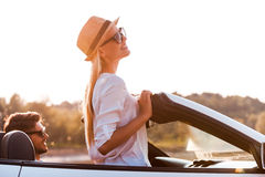 Enjoying the sun and fresh air. Side view of cheerful young women leaning at the wind shield while her boyfriend sitting near on front seat of convertible stock image