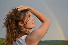 Enjoying the sun after the rain. Beautiful young woman looking at the rainbow on the sky after the rain has passed and the sun has returned Royalty Free Stock Photos