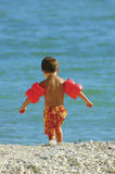 Enjoying a sunny day on the beach. A child on the beach running towards the water Stock Image