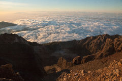 Enjoying sunrise view at summit top in high mountain volcano Rinjani. Island Lombok, Indonesia. Stock Photography
