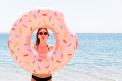 Enjoying suntan. Beautiful crazy woman relaxing and playing with inflatable ring in sea beach. Summer holidays and vacation royalty free stock photo