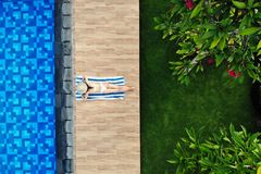 Top view of slim young woman in white bikini and straw hat lying on towel near swimming pool. Back view, without face royalty free stock images