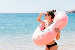 Enjoying suntan and vacation. Portrait of a happy girl looking through inflatable ring stay on the sea beach. Summer holidays. Concept royalty free stock photography