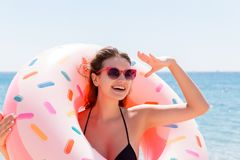 Enjoying suntan and vacation. Portrait of a happy girl looking through inflatable ring stay on the sea beach. Summer holidays. Concept stock photography